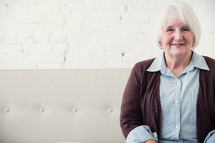 face of an elderly woman sitting on a couch