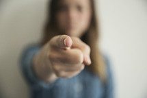 a woman pointing her finger straight at the camera.