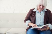 an elderly woman reading the Bible