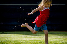 Child running and splashing in a mud puddle.