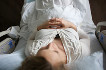 A woman lying in a hospital bed.