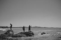 Three fishermen fishing off the coast.