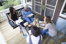Four women having a Bible study on a porch.