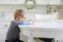 toddler boy praying at a kitchen table