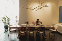 a woman sitting alone at a dining table
