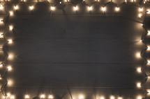 border of Christmas lights on a wood background.