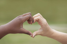 hands from two different races forming a heart shape