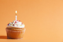 cupcake with candle against an orange background