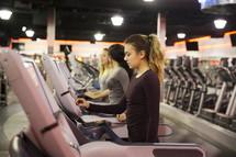 women walking on treadmills at the gym