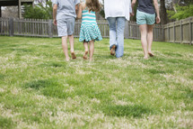 a family walking holding hands in the back yard