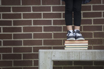 a child on a bench standing on a stack of books while waiting for school to start