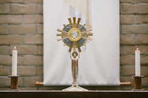 Table with a monstrance and candles in front o a brick wall.