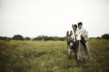Biblical couple in wilderness riding donkey