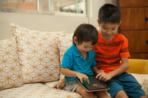 brothers playing on an iPad