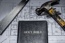 saw, blueprints, and a Bible