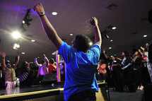 Congregation around center stage with arms raised praising God during worship service.