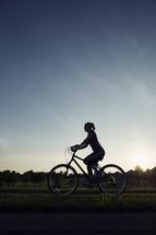 woman riding a bike at sunset