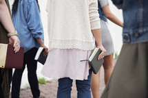A group of young women holding Bibles and walking together.