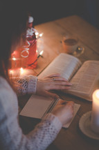a man reading a Bible and writing in a journal at Christmas