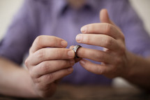 A man taking off his wedding ring.