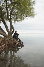 a man sitting on tree roots looking out at water