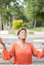 a woman with raised hands praising God sitting on a park bench