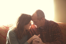 Mature couple praying together in home.