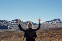 A woman raises her hands to the sky before a mountain range.