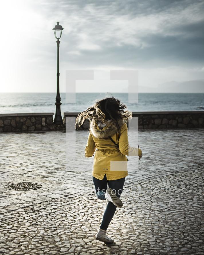 a woman running across stone pavers