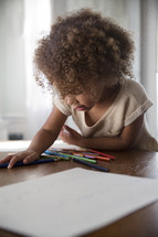 girl coloring at the kitchen table