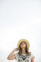 woman in a straw hat looking up to God