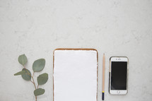 iPhone, notepad, paper, pencil, and eucalyptus leaves, on a white background