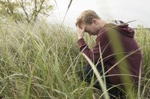 a man squatting in tall grasses and praying deeply