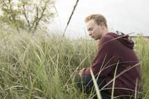 a man sitting in tall grass and praying quietly
