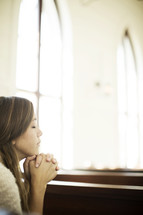 a woman with praying hands at church