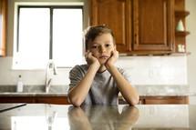 a pouting little boy in a kitchen