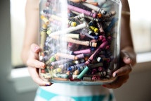 a girl holding a jar of crayons