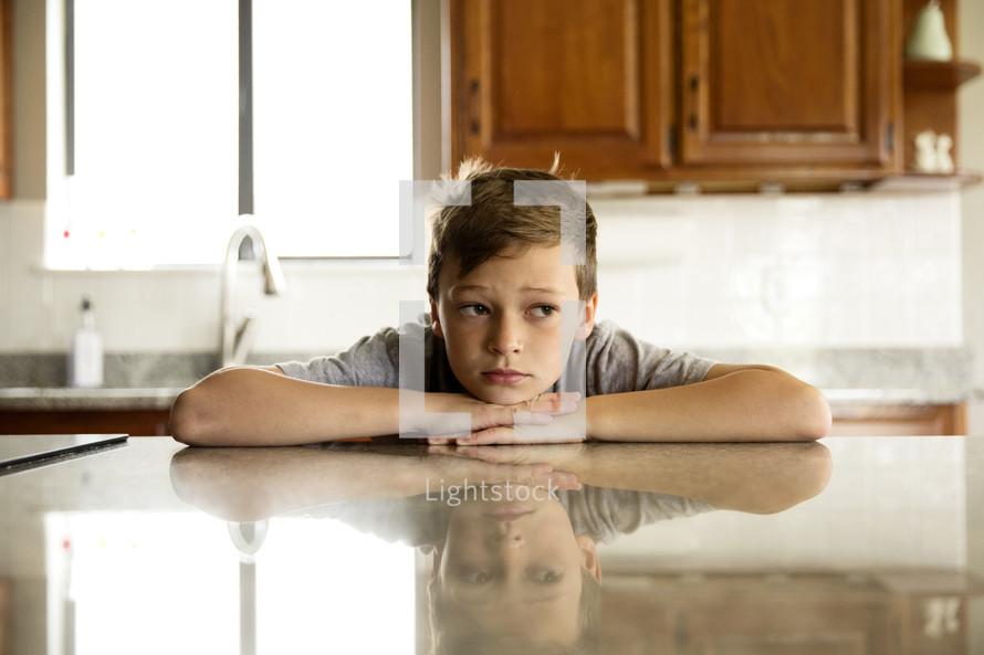 a pouting boy in a kitchen