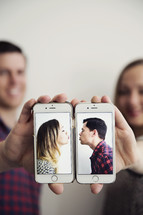 kissing couple on cellphone screens