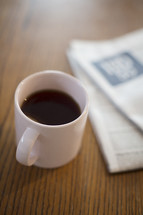A cup of coffee next to a newspaper on a table.