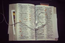 earbuds on the pages of a Bible