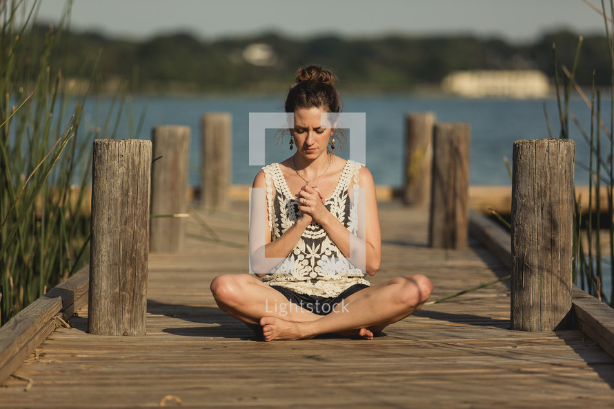 girl praying on a pier