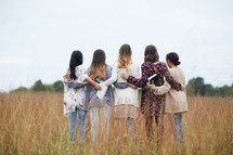group of women walking through a field holding Bibles