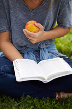 a person sitting in the grass reading a Bible holding a peach