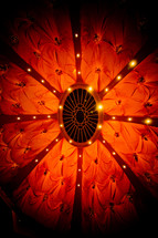 lights at the top of a red fabric tent