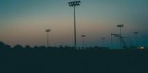 stadium lights over soccer fields at dusk