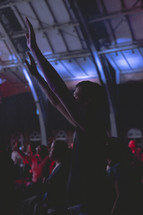 a man standing with raised hands at a worship service