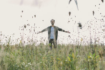 a man standing in a field with open arms