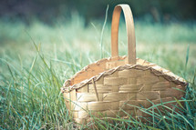 Empty gold Easter basket sitting in grass