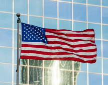 An American flag and reflection in windows of a skyscraper
